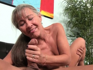 Mature granny tugging cock on couch
