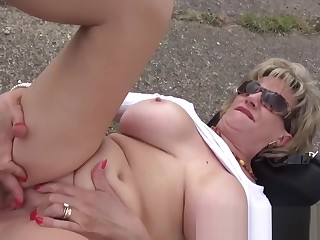 Mature blonde Lady Sonia masturbates outdoors